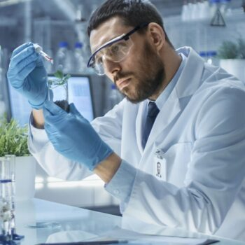 man in lab watering plant