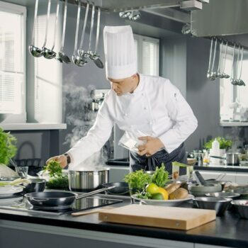 chef cooking in kitchen with green vegetables