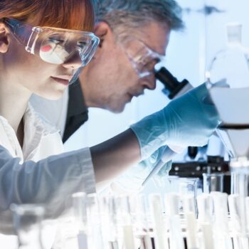 two people in lab microscope